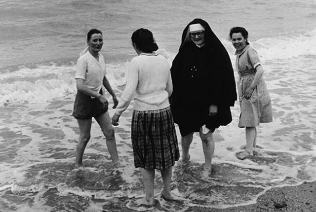 A Roman Catholic nun and three other women wade in the surf at the seaside, 1950s. (Photo by Express Newspapers/Getty Images)