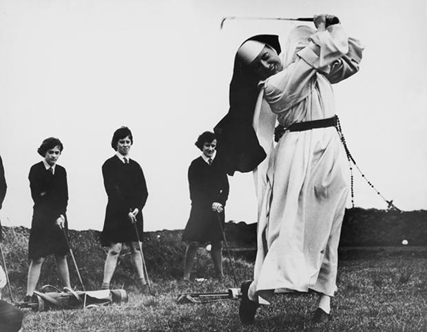 Nun, and golf coach, Sister Mary Martina takes an iron shot on the golf course at Rosebud Country Club, Portsea, Victoria, Australia, 6th September 1965. Looking on are girls from St Mary's School For The Deaf, who, along with Sister Mary Martina, are being coached by the club's proffessionals. (Photo by Central Press/Hulton Archive/Getty Images)